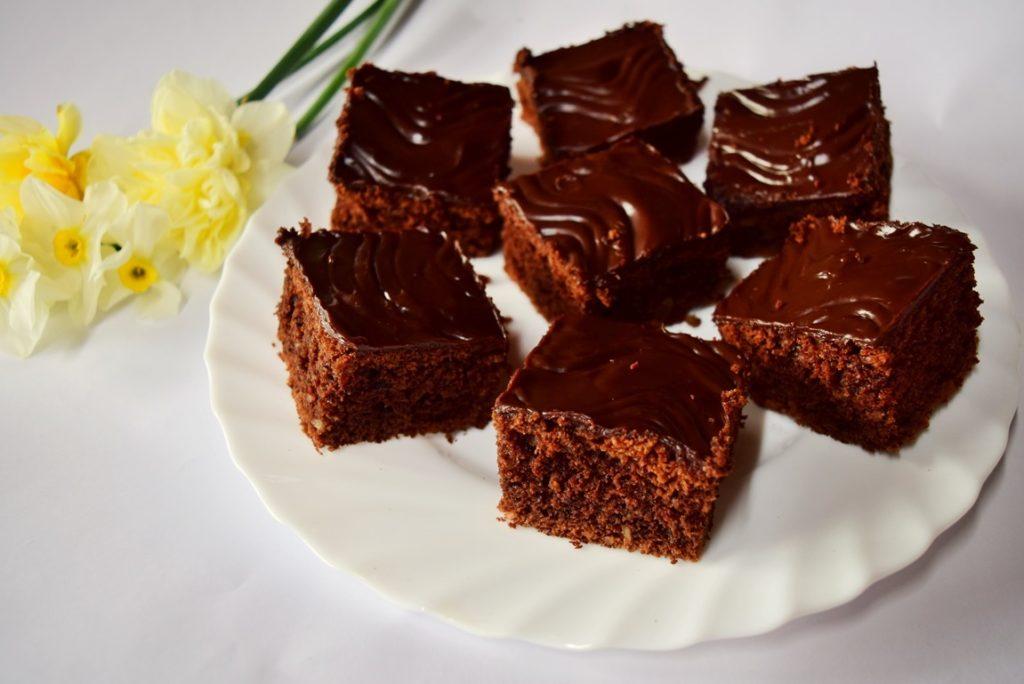 Negresă din albușuri cu glazură de ciocolată, porționată pe un platou alb