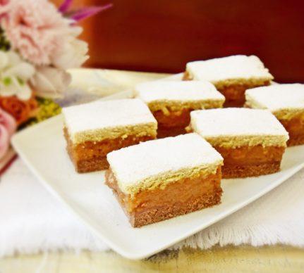 Porții de prăjitură cu mere și aluat bicolor, pe un platou alb, alături de un buchet de flori