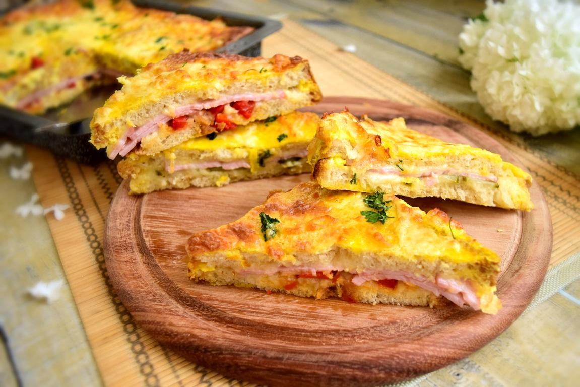 Porții de sandvișuri la cuptor gratinate cu cașcaval și ouă, pe un suport de lemn