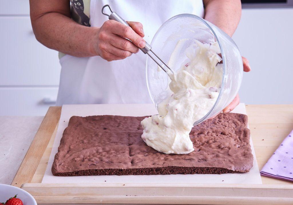 crema de ciocolată albă cu mascarpone și căpșuni se întinde peste foaia de ruladă