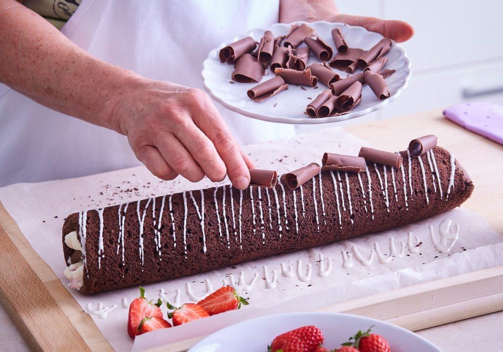Ruladă cu căpșuni și ciocolată albă decorată cu ciocolată neagră