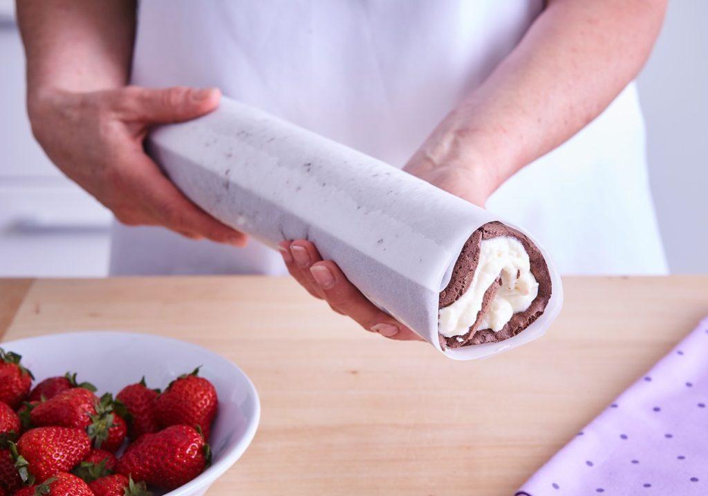 Ruladă cu căpșuni și ciocolată albă împachetată în hârtie de copt