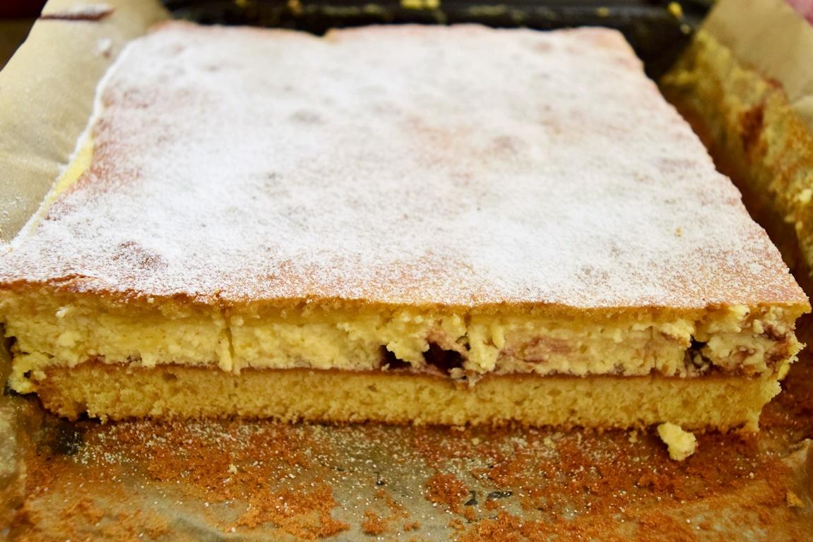Prăjitura turnată cu brânză și stafide, pudrată cu zahăr