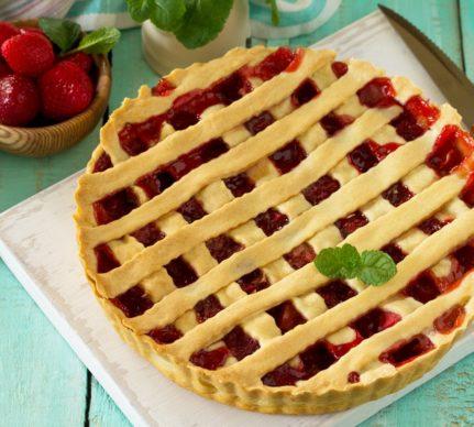Tartă cu căpșuni și mentă, alături de un bol cu căpșuni și un vas cu mentă