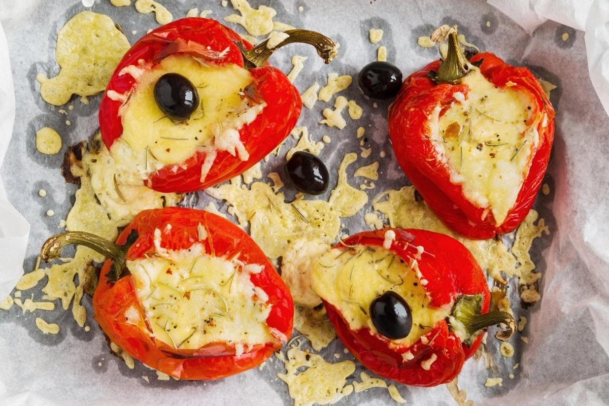 Doi ardei umpluți cu brânză feta și măsline, în tava de copt