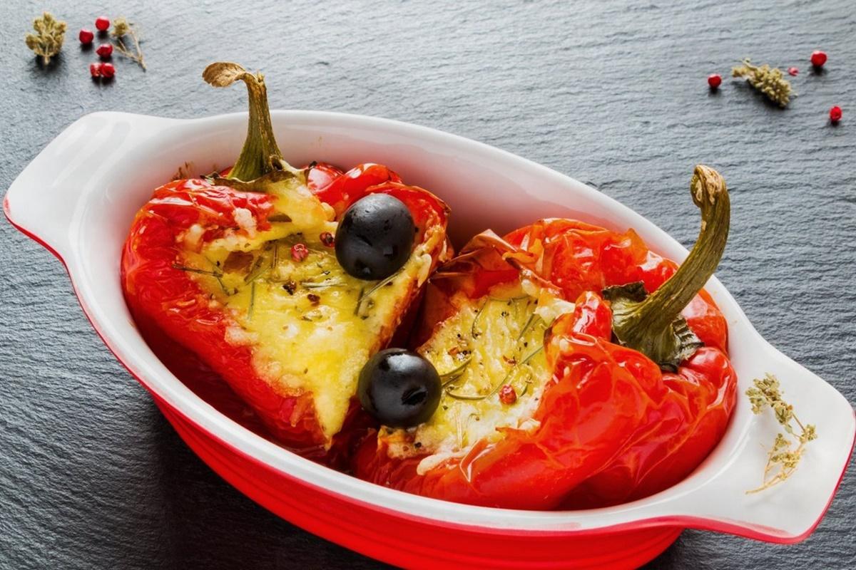 Doi ardei umpluți cu brânză feta și două măsline, într-un vas ceramic, oval