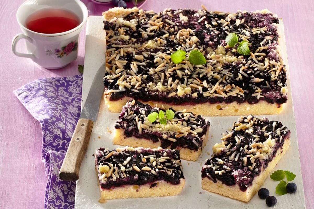 Prăjitură cu afine și crumble cu migdale, porționată și decorată cu frunze de mentă