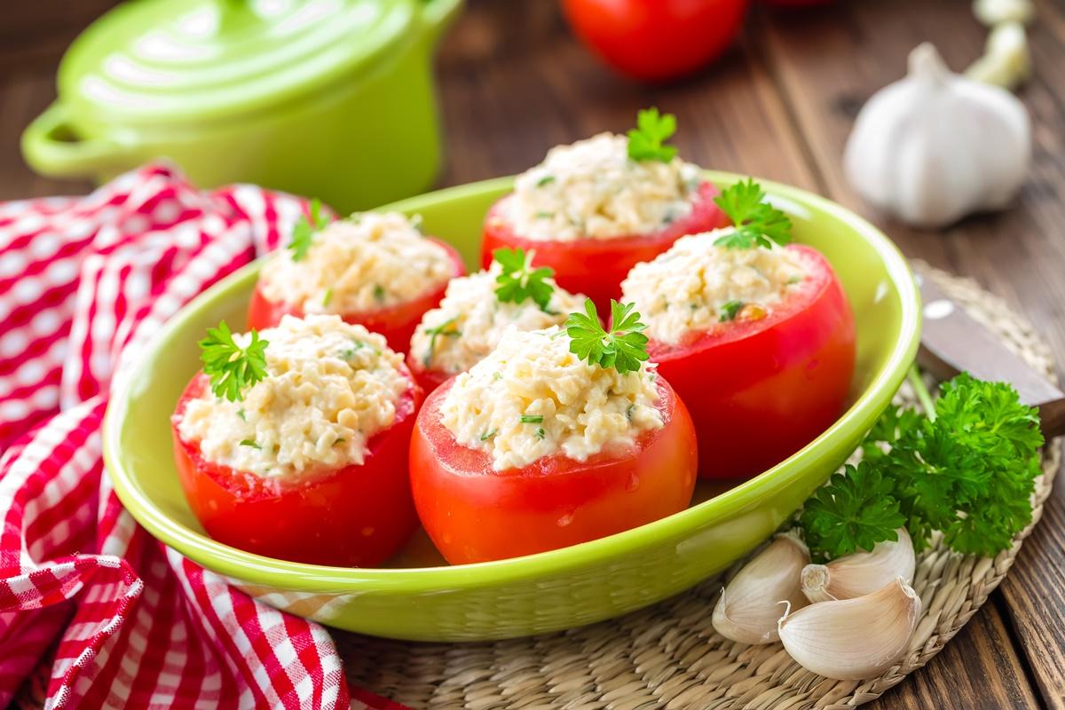 Roșii umplute cu brânzeturi și condimente, într-un bol verde