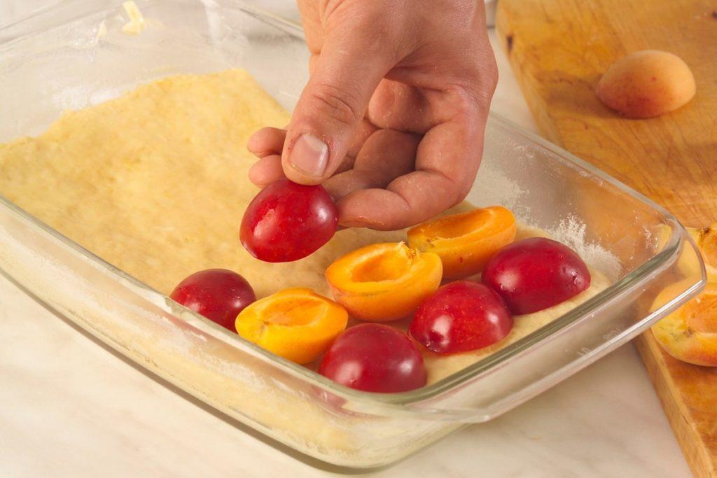 Pasul de așezare al fructelor peste aluat fraged la prăjitura cu prune și caise