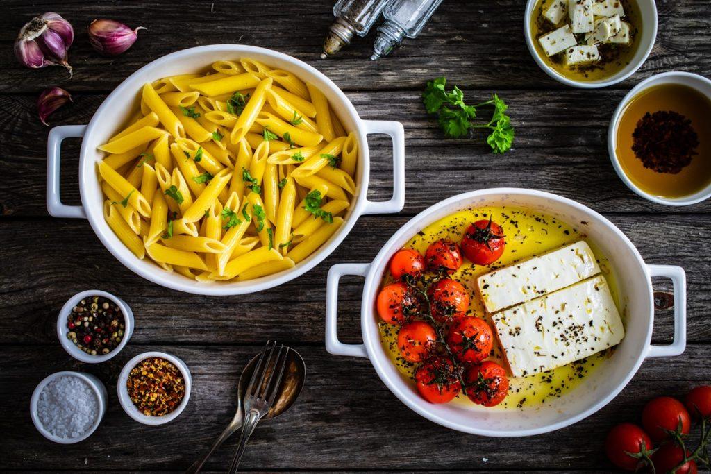 Roșii cherry cu brânză feta în ulei de măsline aromatizat, în bol de ceramică, alături de paste cu busuioc în alt bol
