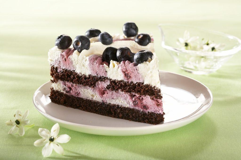 Felie de tort cu cremă de afine și mascarpone pe o farfurie albă