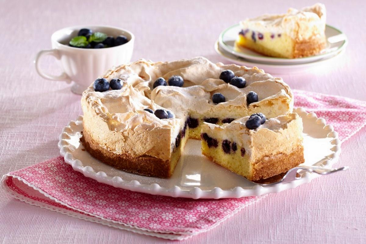 Prăjitură cu afine și bezea, porționată, alături de o ceașcă cu afine