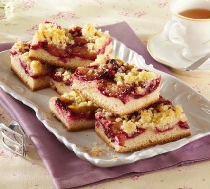 Prăjitură cu prune și crumble porționată, alături de o ceașcă cu ceai