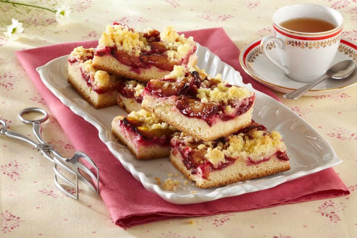 Prăjitură cu prune și crumble porționată pe un platou