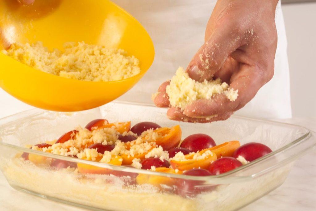 Pasul de distibuire crumble peste fructe la prăjitură cu prune și caise, acoperite cu crumble crocant