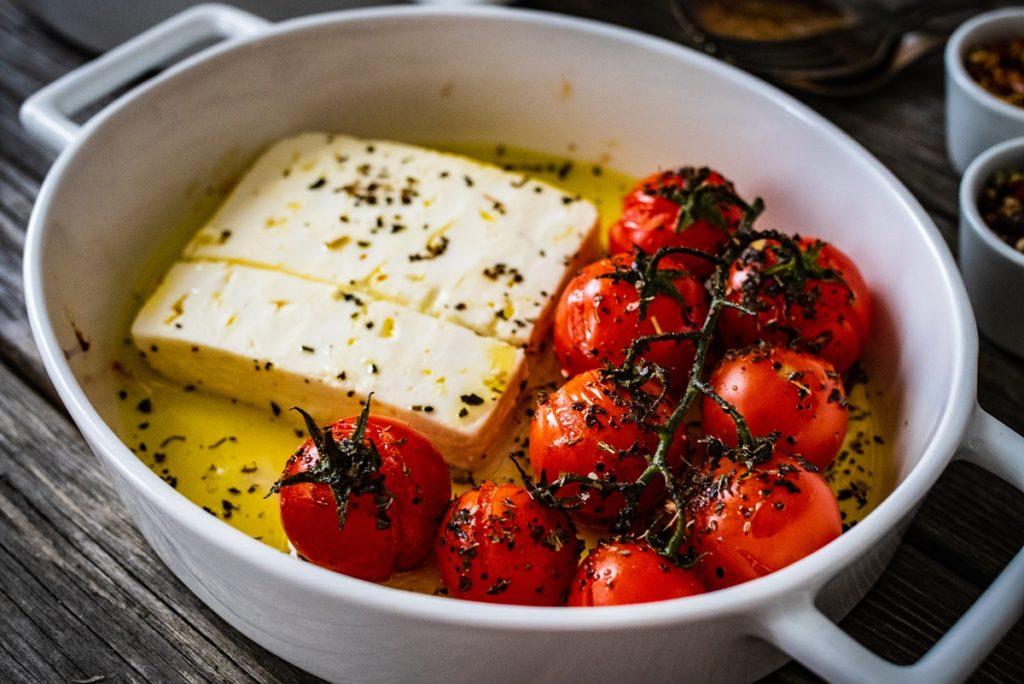 roșii cherry și brânză feta în ulei de măsline, într-un vas alb din ceramică