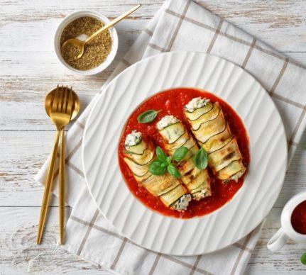 Trei rulouri de dovlecei cu brânză în sos de roșii, într-o farfurie albă, cu tacâmuri pentru servit