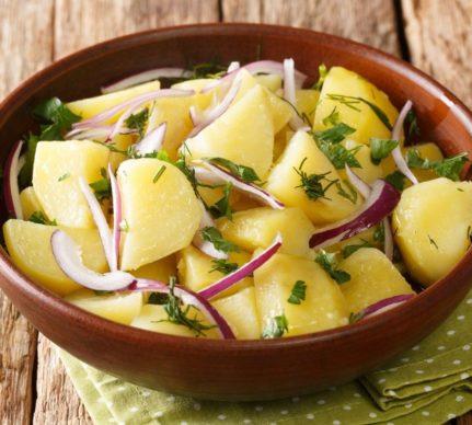 Salată de cartofi cu ceapă roșie într-un bol rustic