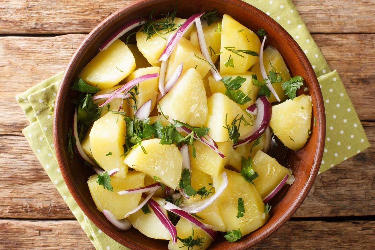 Salată de cartofi cu ceapă roșie, într-un bol maro, pe un ștergar verde cu buline