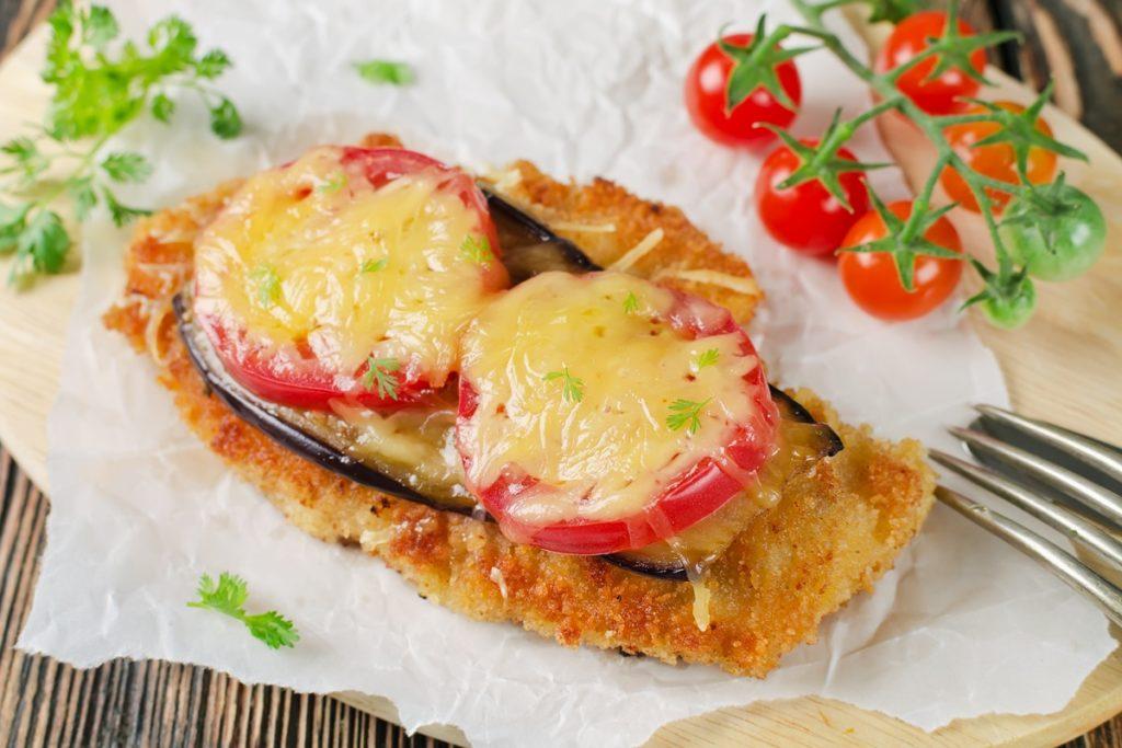 Șnițel de pui cu legume gratinate cu cașcaval, pe o hârtie de copt, alături de o crenguță de roșii cherry
