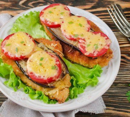 Șnițele de pui cu legume gratinate la cuptor, pe o farfurie albă cu salată verde
