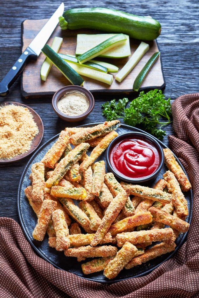 Poză cu sticksuri de dovlecei pe un platou de servire, alături de un bol cu ketchup, iar în spate, ingredientele necesare rețetei