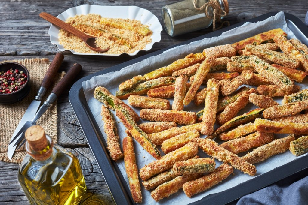 Sticksuri de dovlecei cu pesmet și parmezan în tava aragazului, alături de ingredientele folosite