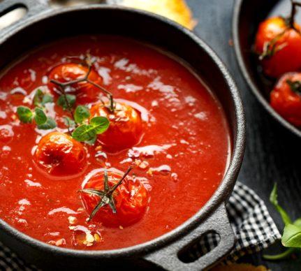 Supă cremă de roșii coapte cu ardei copți, decorată cu o crenguță de roșii cherry