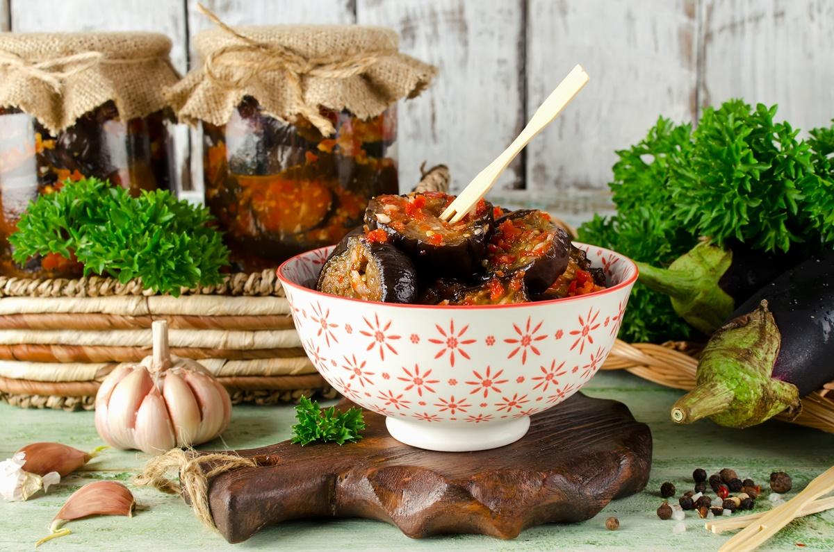 Vinete marinate în sos de roșii cu usturoi și ardei, într-un bol de servire și în borcane