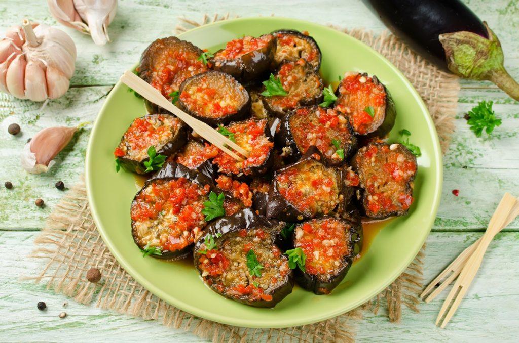 Vinete marinate în sos de roșii cu usturoi, pe o farfurie verde