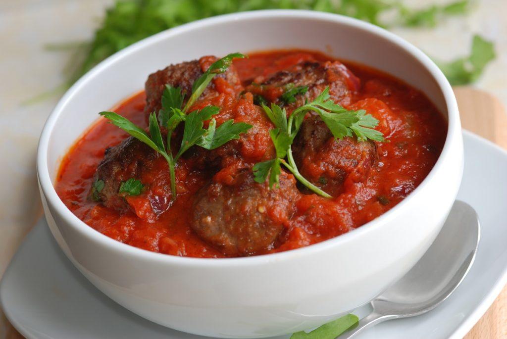 Bol alb cu o porție de chiftele la cuptor în sos de roșii cu usturoi
