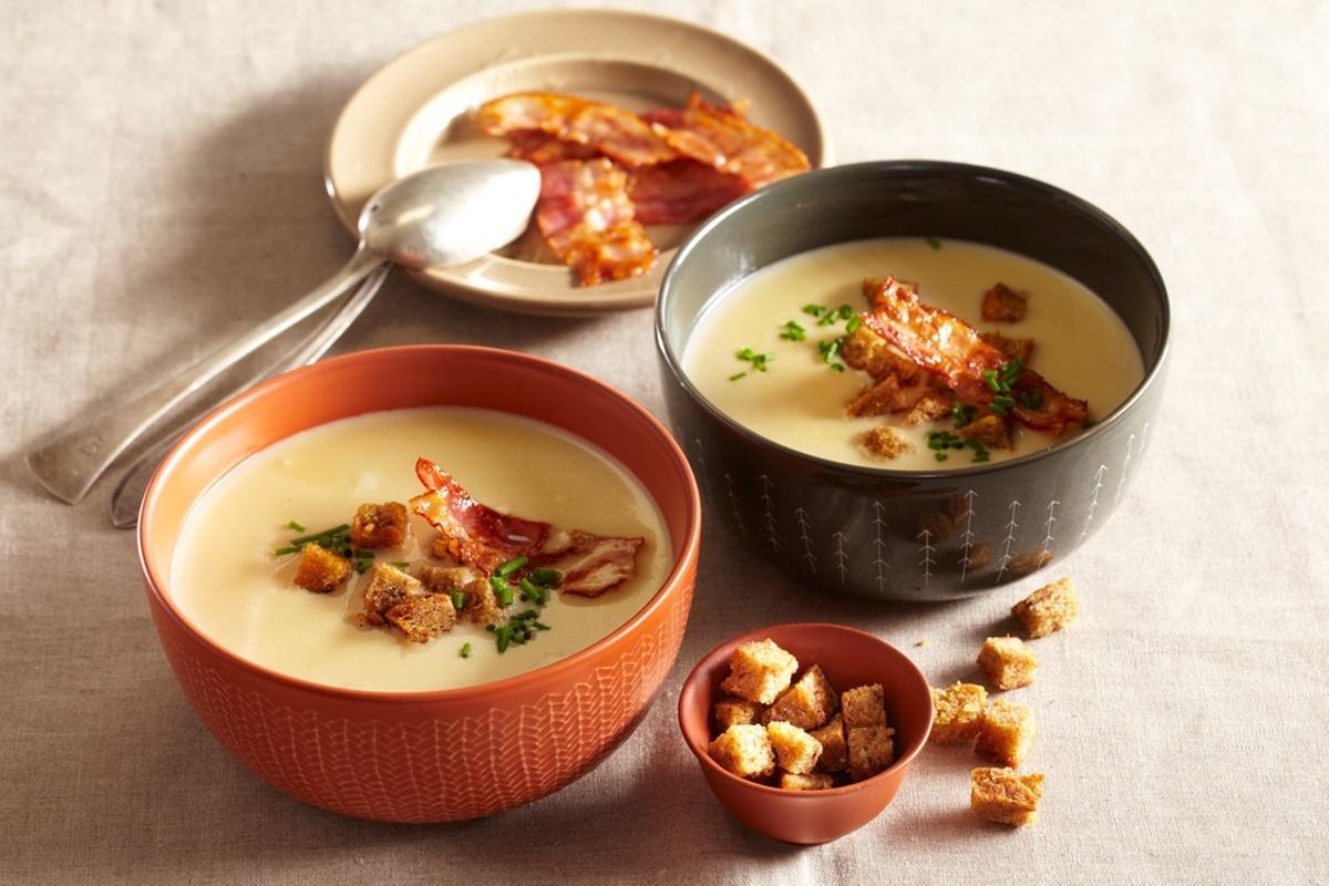 Două boluri cu Supă cremă de usturoi cu bacon și crutoane, alături de o farfurie cu felii de bacon