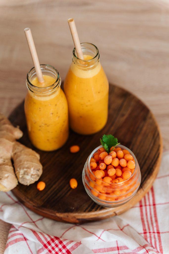 Două sticle cu smoothie de cătină pentru a prepara Nectar de cătină cu miere și ghimbir