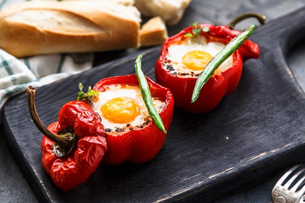 Ouă ochiuri în ardei pe un platou negru, alături de pâine și ardei iuți