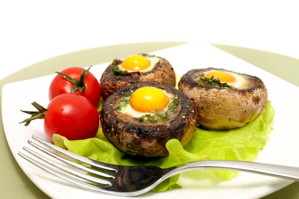 Ouă ochiuri în ciuperci pe foi de salată verde, alături de roșii proaspete