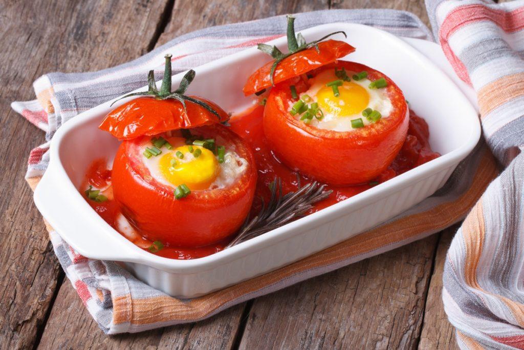 Ouă ochiuri în roșii, servite cu sos de roșii într-un vas alb, dreptunghiular