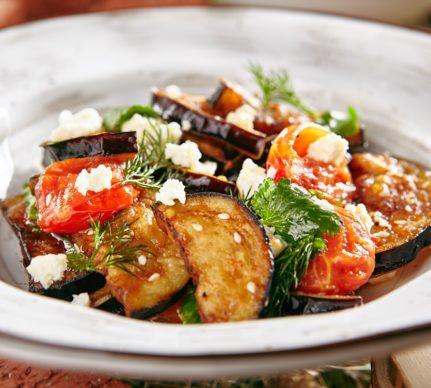 Salată de vinete cu roșii și brânză, decorată cu susan, mărar verde și pătrunjel verde