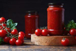 Două borcane cu Sos de roșii pentru paste și pizza, alături de roșii cherry și busuioc