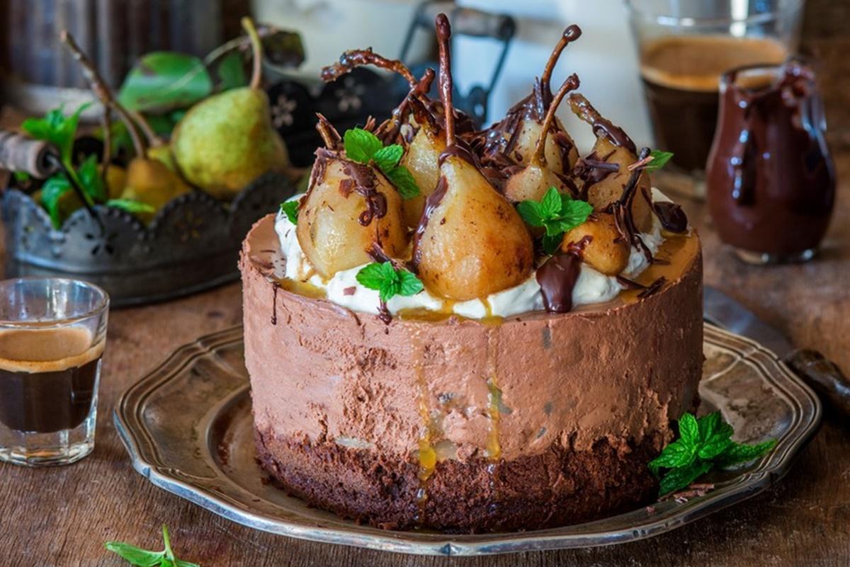 Tort cu mousse de ciocolată și pere poșate în vin roșu, pe un platou de servire