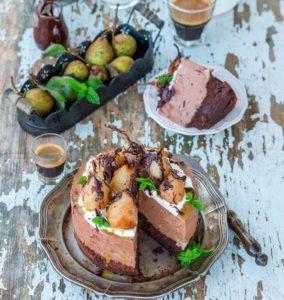 Tort cu mousse de ciocolată și pere poșate în vin roșu, porționat, alături de un platou cu pere