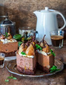 Tort cu mousse de ciocolată și pere poșate în vin roșu, secționat, alături de un ceainic alb