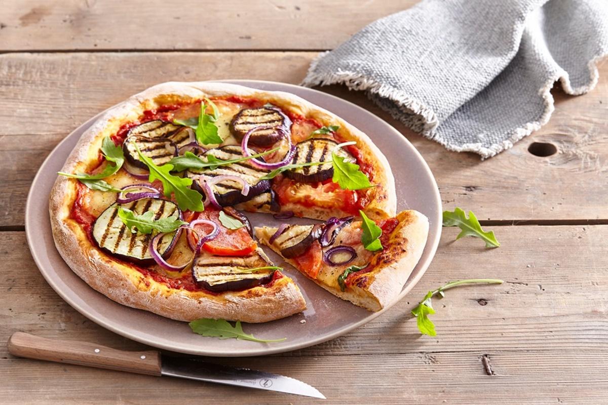 Pizza cu vinete, mozzarella, ceapă roșie și rucola, pe o farfurie albă