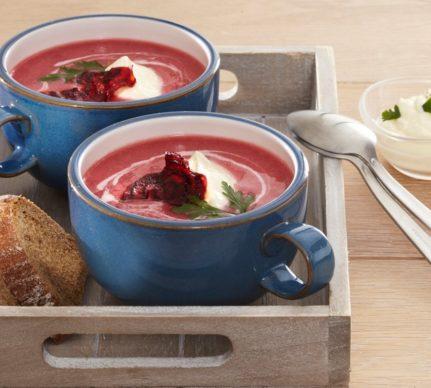 Două porții de Supă cremă de sfeclă roșie cu smântână în două boluri albaste așezate într-o tavă de lemn